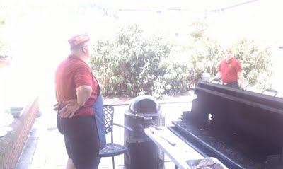 Bruce is grilling burgers, while Tim sets up the gear....